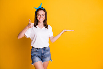 Photo of beautiful brown haired girl show empty space thumbs up approve wear blue pin up white t-shirt isolated on yellow color background Wall mural