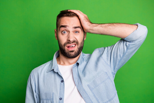 Portrait of upset guy hand head wear blue shirt isolated on vibrant green color background