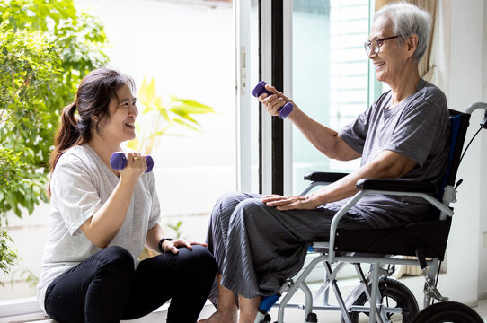 Asian caregiver is doing physical therapy for the old elderly,disabled senior woman in a wheelchair,exercise use dumbbells to help strengthen the muscles of hands,arms and shoulders,workout at home