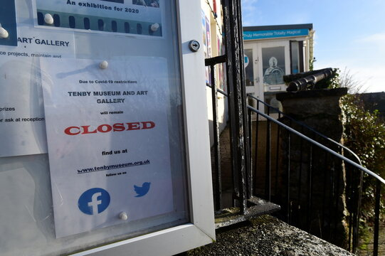 A closed sign is placed outside the Tenby Museum and Art Gallery in Tenby, Wales