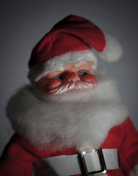 Closeup of a vintage 1950s creepy Santa Claus doll with red cap and coat and white beard