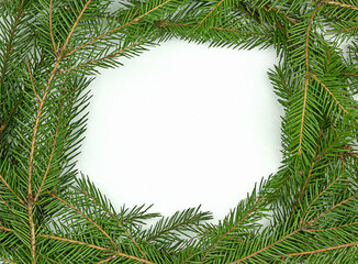 Frame of traditional natural green Christmas branches on white background. Top view with copy space for text, gifts and toys.