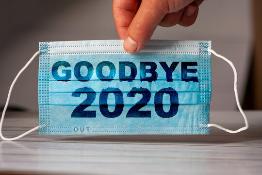 hand holds a medical and protective mask with the word GOODBYE 2020. Concept of coronavirus quarantine. Prevent or stop the spread of the COVID-19 worldwide.