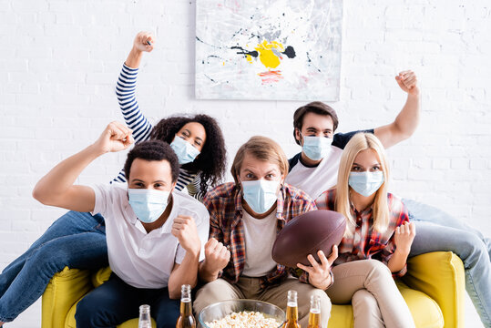 excited multicultural friends in medical masks showing win gesture while watching rugby championship