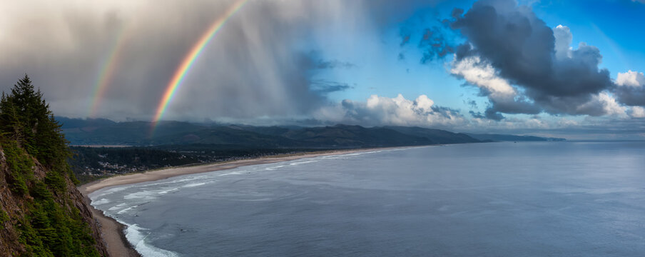 Manzanita, Oregon, United States. Aerial Panoramic View of a small town and a sandy beach on the the Pacific Ocean Coast. Cloudy Rainy summer day with Rainbow.