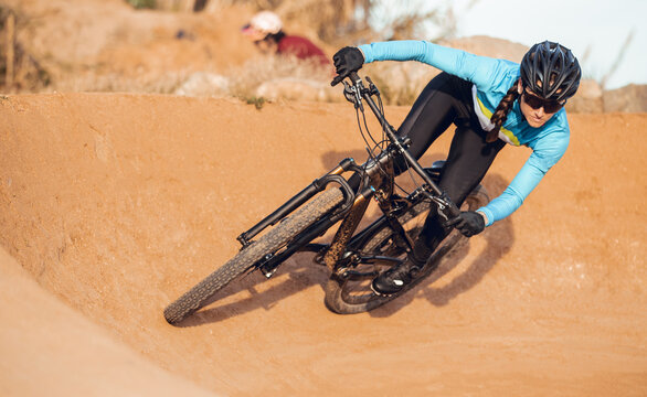 Sportswoman in black helmet and blue sportswear with glasses riding mountain bike on training track
