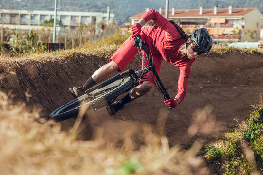 Sportswoman in black helmet and red sportswear with glasses riding mountain bike on training track