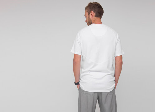 young stylish male doctor in white t-shirt and gray pants is standing from the back with hands in pockets on the white wall background. medical concept. free space on left side, mockup