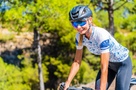 Cheerful active young female bicyclist in sportswear and protective helmet and goggles riding bike near green trees in sunny summer day in nature