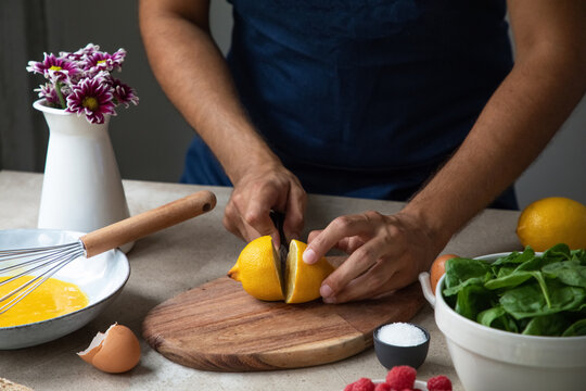 Crop anonymous male cook cutting fresh lemon on wooden board while preparing healthy dish with natural ingredients in kitchen