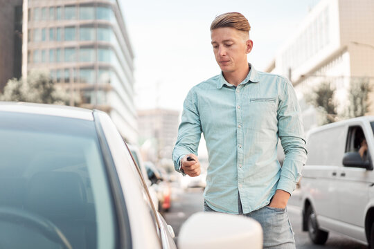 Handsome male driver unlocking doors of modern automobile with remote control key while standing on parking in city
