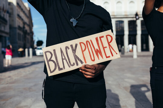 """Anonymous man protesting at a rally for racial equality holding a """"Black Power"""" poster. Black Lives Matter."""