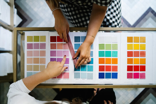 Top view of unrecognizable female designers standing at table in bright studio and choosing color of textile samples