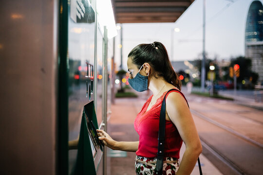 Side view of young female passenger in protective mask buying ticket for public transport on vending machine