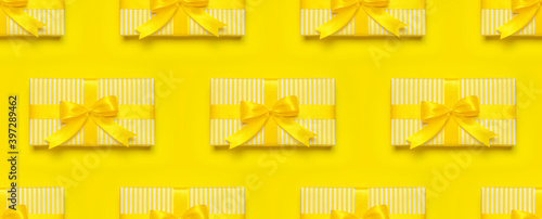 Seamless Pattern of yellow gift present box with ribbon and bow on yellow background top view copy space. Flat lay holiday background. Birthday present, March 8, Mother's Day, Valentine's Day