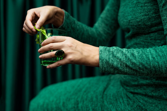 Midsection of woman holding glass of cocktail drink sitting against curtain