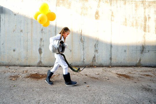 Little girl walking with space helmet and holding balloon on street during sunny day