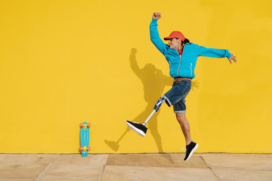 Happy disabled man walking against yellow wall
