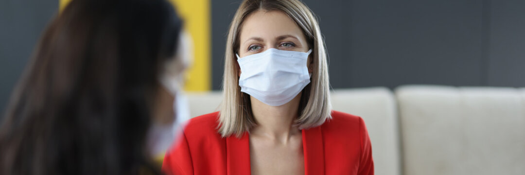 Women in medical protective masks communicate in office.