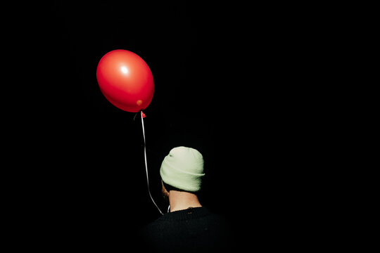 anonymous person in cap with red balloon in the dark