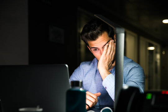 Tired businessman working late in office