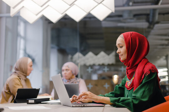 Cheerful Islamic businesswoman using laptop in modern workplace