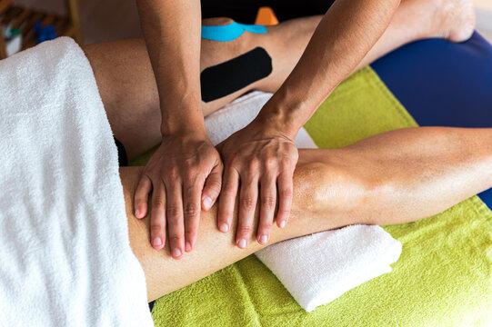 Crop therapist massaging knee of patient