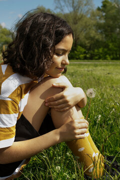 Cute girl sits on a grass with a dandelion