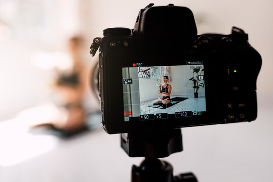Professional camera recording video of woman meditating in lotus pose with singing bowl