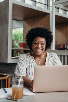 Positive black lady using laptop in coworking space