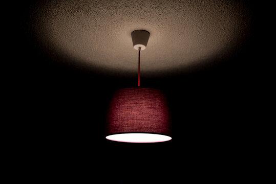 purple ceiling lamp lit in dark room