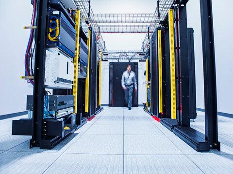 Blurred view of Hispanic technician walking in server room