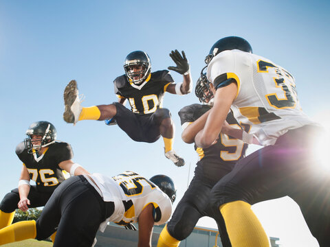 Football player leaping over players on football field