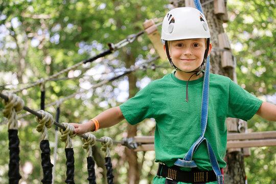 Caucasian boy balancing on rope bridge