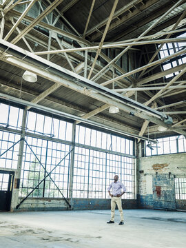 Black businessman standing in empty warehouse