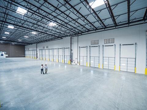 Businessmen walking near loading docks in empty warehouse