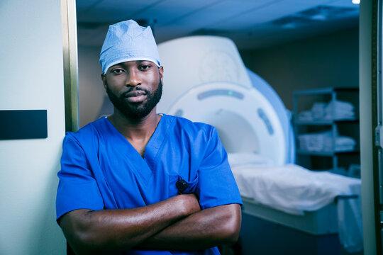 Portrait of confident black nurse near scanner