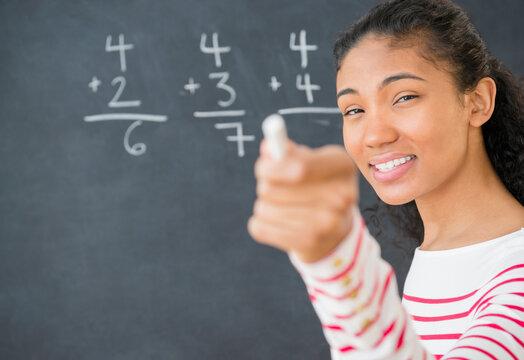 Mixed race teacher doing math on chalkboard