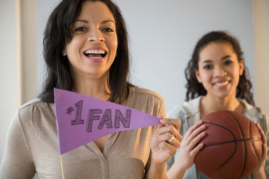 Mother holding fan flag for athlete daughter