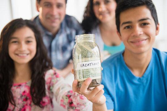 Hispanic family holding full vacation savings jar