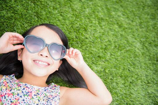Filipino girl wearing sunglasses in backyard