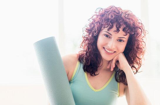 Hispanic woman holding yoga mat