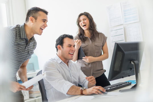 Hispanic business people laughing together in office