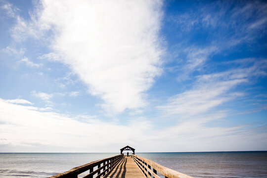 Wooden pier under blue sky over ocean
