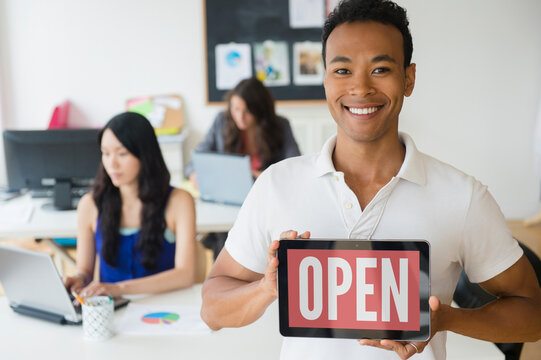 Businessman holding open sign on digital tablet in office