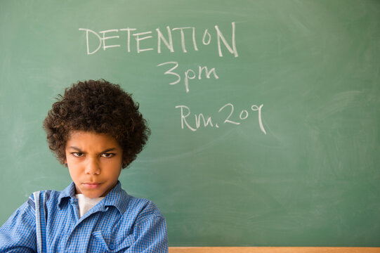 Angry mixed race boy frowning in classroom detention