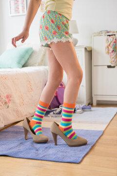 Caucasian girl wearing high heels in bedroom