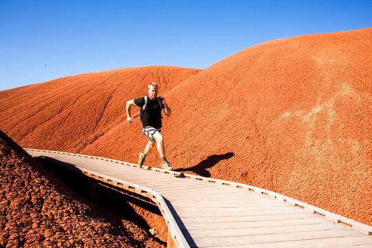 Caucasian man running on walkway in desert hills