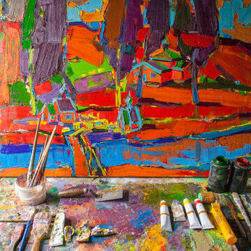 Painting on easel with paint and paintbrushes