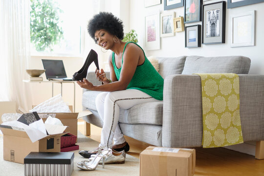 African American woman opening packages of shoes on sofa